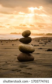Zen stones on beach, pile of stones by the sea. Balance stones are arranged in a pyramid shape