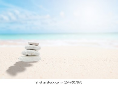 Zen stones on the beach for relaxing meditation. Pyramid stones with sun and blurred background