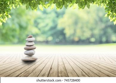 Zen камни на пустой деревянный с зеленым листом на фоне сада размыто и. Концепция релаксации, дзен, весна.