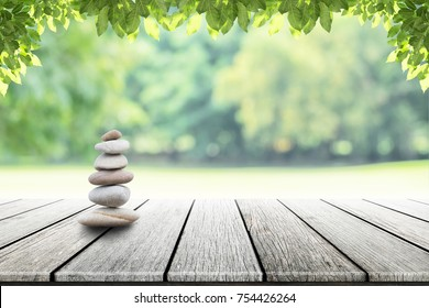 zen stones on empty wooden with green leaf in the garden background blurred. Concept relaxation, zen, spring.