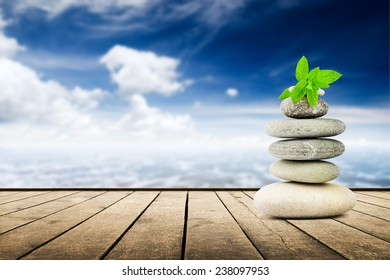 zen stones on the old wooden planks over seascape background