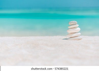 Zen stones on tropical beach for perfect meditation. Stones pyramid on soft sandy beach symbolizing stability, zen, relaxation, harmony, balance, inspirational, sea, peace. Shallow depth of field.