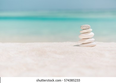 Zen stones on tropical beach for perfect meditation. Stones pyramid on soft sandy beach symbolizing calm and relaxation