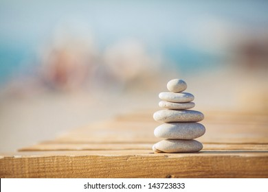 zen stones on wooden banch on the beach near sea. Outdoor. en style path on vintage wood table in relaxing wellness holistic spa for relaxation and good health rejuvenation