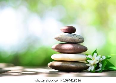 Zen stones and orange jasmine on wooden floor with green natural bokeh left space position.