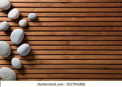 zen stones set on design wooden board for concept of spa, massage, mindfulness or wellbeing, copy space still life, top view