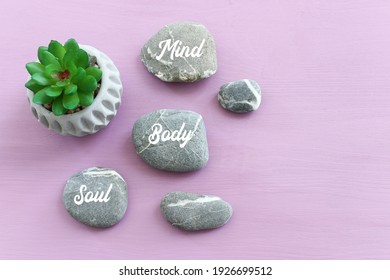 zen stones with the words Mind body soul. purple wooden background
