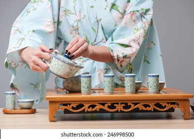 Zen tea setting. Closeup portrait of tea ceremony performed with tea tools on wooden table by beautiful Japanese woman