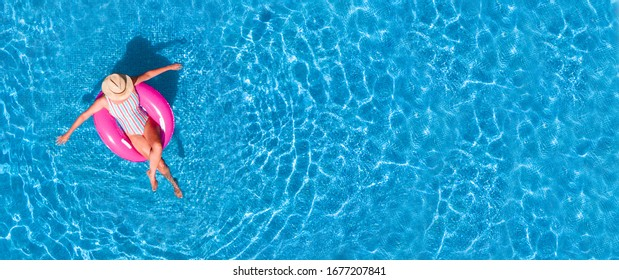 Zenith aerial view of a swimming pool in summer. Young girl in a swimsuit and hat floating with pink donut.