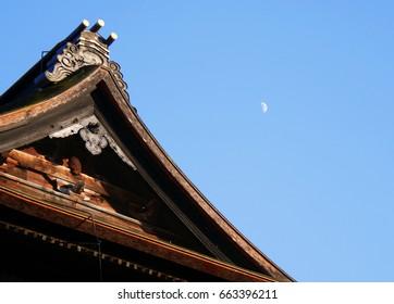 Zenkoji temple's roof with half moon and blue sky Nagano Japan
