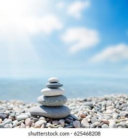 zen-like stones on beach under sun. soft focus