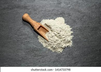 Zeolite mesolite raw powder and spoon on black stone  background.Macro shot