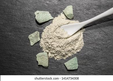 Zeolite natural raw stones and zeolite mesolite powder on black stone  background.Macro shot