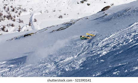 Zermatt backcountry laying on the snow upside down with skis in the air after the jump.