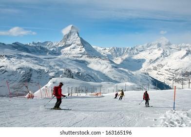 ZERMATT - JANUARY 17: Skiers Skiers downhill skiing from Gornergrat station on January 17, 2013 in Switzerland. The mountain village of Zermatt is one of the great ski center of the world.