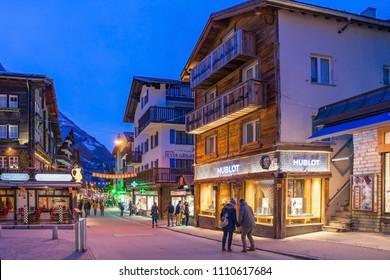 ZERMATT, SWITZERLAND - APRIL 11, 2018: Tourists at street view of old town Zermatt in twilight time in the center in Zermatt, Valais canton in Switzerland.