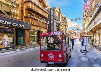 ZERMATT, SWITZERLAND - APRIL 11, 2018: Unidentified man drives electric delivery car by the main street of Zermatt, Switzerland. Zermatt is a combustion-engine car-free zone.