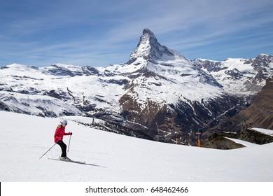 Zermatt, Switzerland - April 12, 2017: A woman skiing in front of the famous Matterhorn