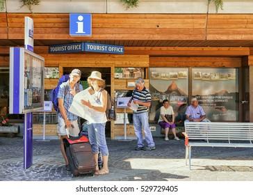 Zermatt, Switzerland - August 24, 2016: Tourists looking into the city map at the tourist offcie in Zermatt in Switzerland.