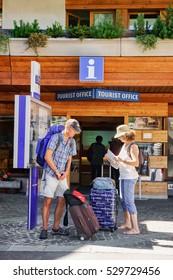 Zermatt, Switzerland - August 24, 2016: Tourists looking into the city map near the tourist offcie of Zermatt in Switzerland.