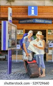 Zermatt, Switzerland - August 24, 2016: Tourists looking into the city map at the tourist offcie of Zermatt in Switzerland.