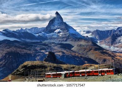 Zermatt Switzerland. Famous electric red tourist train coming down  in Zermatt Valais region Switzerland Europe.