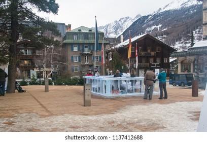 Zermatt, Switzerland -Feb, 2018: Cityscape of Tourists at street view of old town Zermatt and ice bar in twilight time in the center in Zermatt, The UNESCO World Heritage. Valais canton in Switzerland