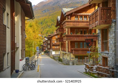 ZERMATT, SWITZERLAND, OCTOBER 20, 2010: View on village street with traditional Swiss chalets cottages style among fall color Alpine mountains and and Matterhorn peak. Mountain village cityscape