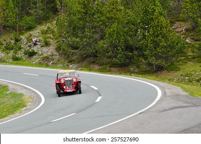 ZERNEZ, SWITZERLAND - JUNE 15: A red MG TC takes part to the Summer Marathon classic car race on June 15, 2014 near Zernez. This car was built in 1948