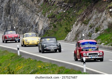 ZERNEZ, SWITZERLAND - JUNE 15: A Volvo PV544, a Daimler SP250, a Porsche 356 and a Alfa Romeo Giulia take part to the Summer Marathon on June 15, 2014 near Zernez. Cars built in 1965, 1960, 1964, 1963