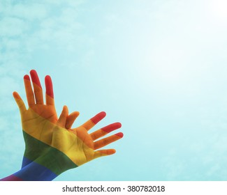 Zero discrimination day concept with rainbow flag pattern on people's hand in butterfly shape