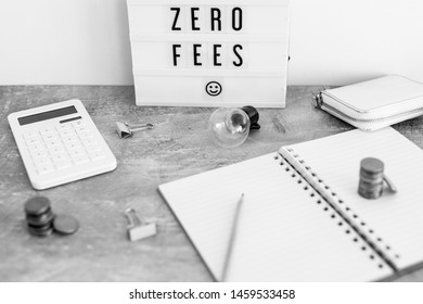 zero fees message on lightbox surrounded by coins calculator on office stationery on concrete desk, black and white