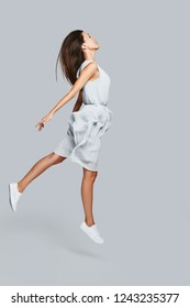 Zero gravity. Full length of beautiful young Asian woman hovering against grey background