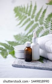 Zero waste bathroom accessories, natural sisal brush, aroma oil, metal jar, cotton towel, essential oil on marble plate, minimal eco-friendly background, minimal stylish set