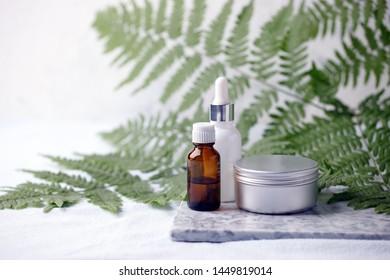 Zero waste bathroom accessories, natural sisal brush, aroma oil, metal jar, essential oil on marble plate, minimal eco-friendly background, minimal stylish set