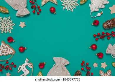 Zero waste Christmas composition with glass, textile and wooden decorations, pine cones, present bags, berries on teal background. Flat lay top view