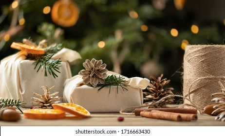 Zero waste christmas concept. Packed in natural fabric gifts and decorations from natural materials on wooden table near Christmas tree with lights