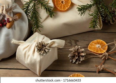 Zero waste christmas concept. Packed in natural fabric gifts and decorations from natural materials on a wooden table