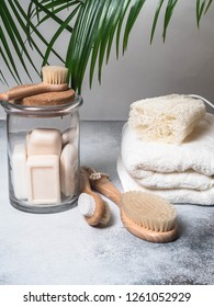 Zero waste concept. Eco-friendly bath set. Brushes, soap in jar, towel, pumice and bast and palm leafs
