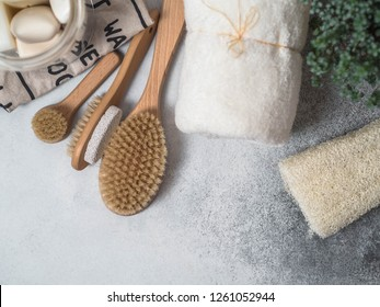 Zero waste concept. Eco-friendly bath set. Brushes, soap in jar, towel, pumice and bast and plant in wood flowerpot. Top view. Copy space
