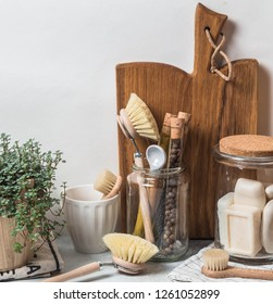 Zero waste concept. Eco-friendly kitchen set. Brushes, soap in jar, spices in glass tubes and plant in wood flowerpot Copy space