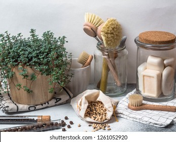 Zero waste concept. Eco-friendly kitchen set. Brushes, soap in jar, spices in glass tubes, beans in cloth bag and plant in wood flowerpot