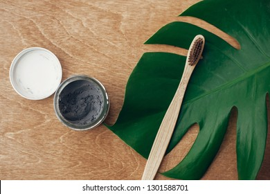 Zero waste concept. Natural toothpaste activated charcoal in glass jar and bamboo toothbrush on wooden background with green monstera leaf. Plastic free essentials, teeth care. Sustainable lifestyle