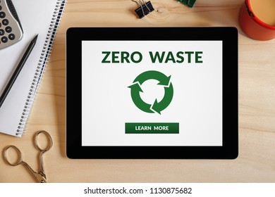 Zero waste concept on tablet screen with office objects on wooden desk. All screen content is designed by me. Top view
