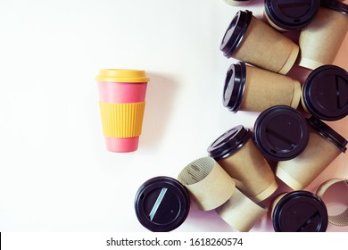Zero waste concept Stylish reusable eco coffee cup and multiple single use cardboard cups. Ban single use plastic. Sustainable lifestyle flat layout