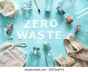 Zero waste concept. Textile eco bags, glass jars and bamboo toothbrush on blue background with Zero Waste white paper text in center. Eco friendly and reuse concept. Top view or flat lay