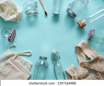 Zero waste concept. Textile eco bags, glass jars and bamboo toothbrush on blue background with copy space for text in center. Eco friendly and reuse concept. Top view or flat lay