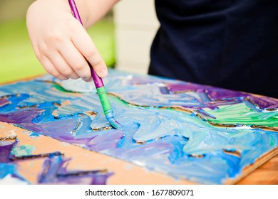 Zero waste. Corrugated cardboard cut  and glued to make terrain. boy painting it to look like sea. DIY games at home. save the ocean concept.