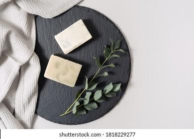 Zero-Abfall-Kosmetik-Konzept. Flachlag, Draufsicht von natürlicher, organischer, handgefertigter Seife und Eukalyptus-Pflanze bei Handtuch auf schwarzem Teller auf weißem Kopienhintergrund