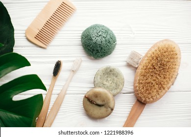 Zero waste flat lay. Natural solid shampoo bar, bamboo toothbrushes, wooden brush,  deodorant cream and konjaku sponge on white wood with green monstera leaves. Eco products plastic free
